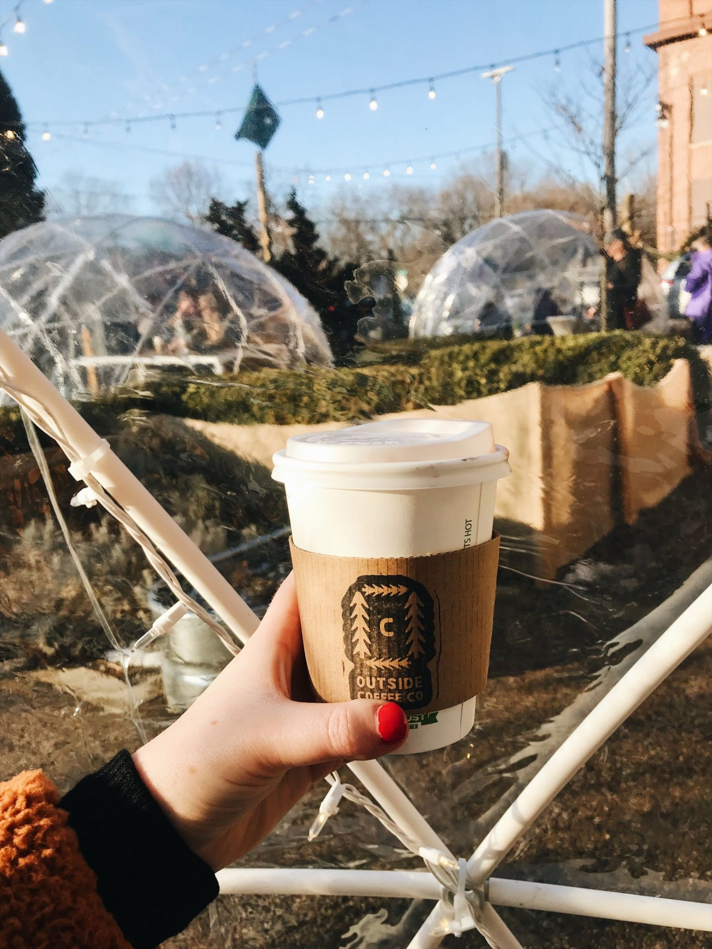 hand holding coffee cup out with igloos in background