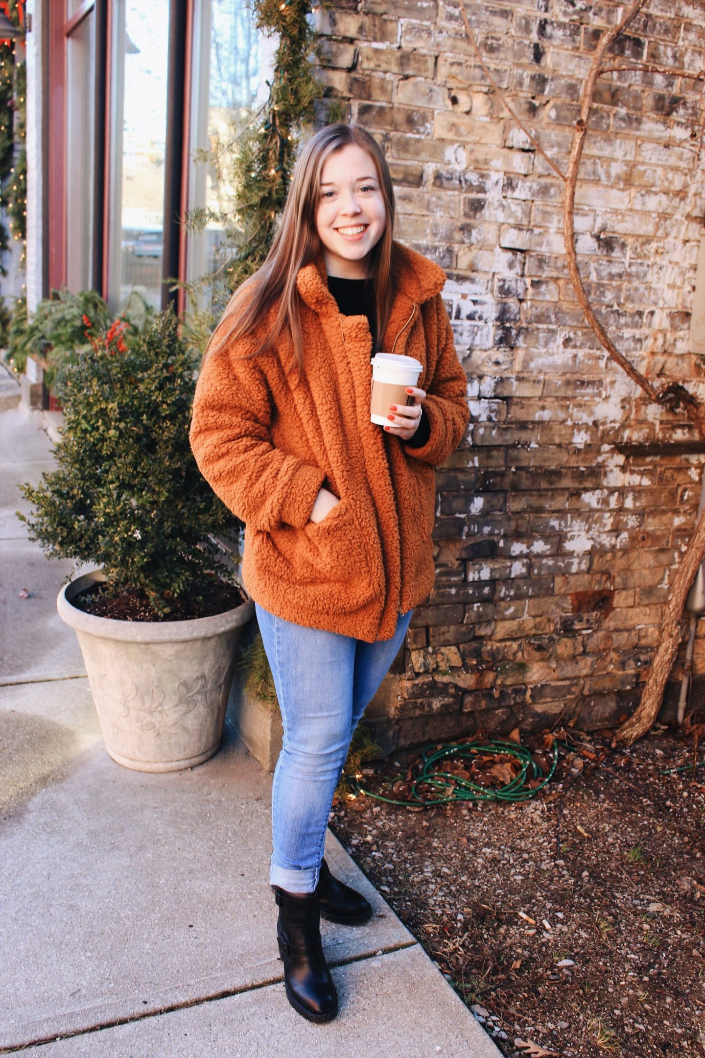 girl standing in front of a brick wall smiling and holding a coffee cup in one hand with her other hand in her coat pocket