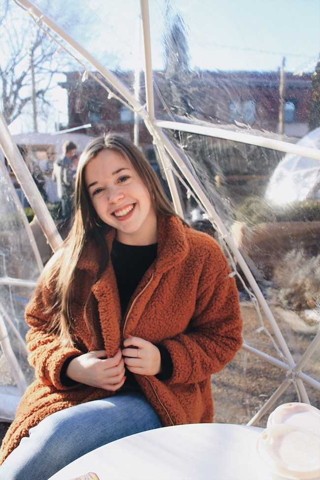 girl with straight brown hair wearing jeans and a fuzzy brown coat sitting in an igloo